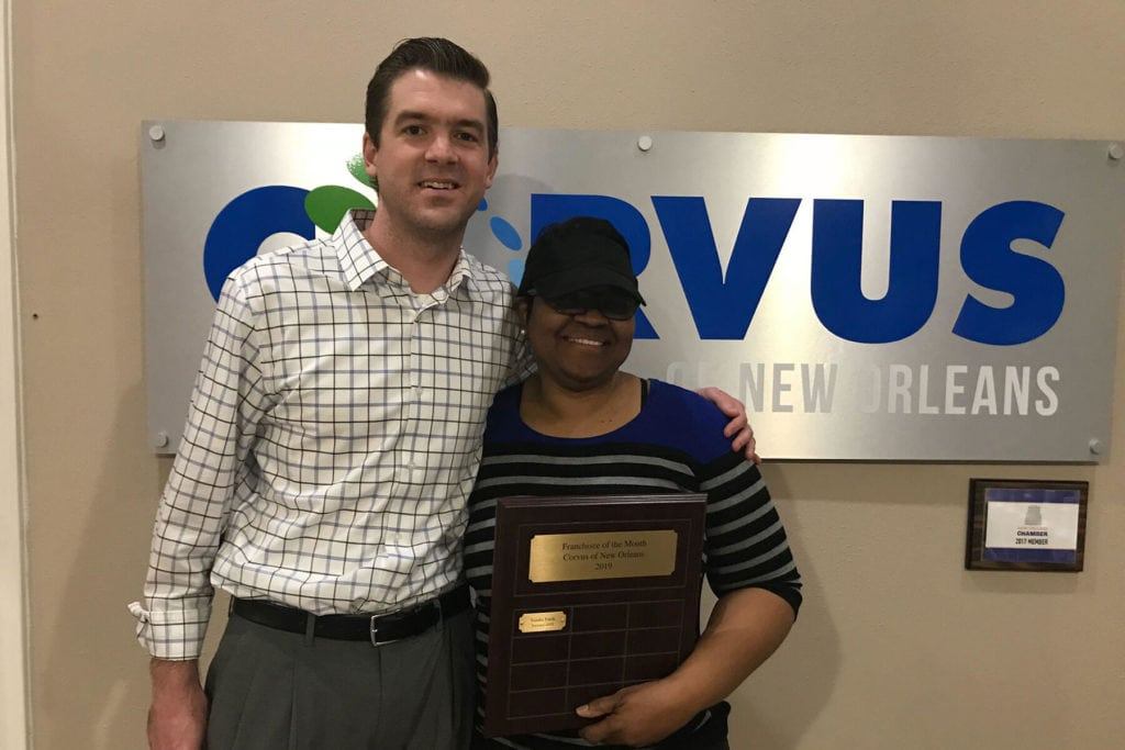 Corvus employee and Corvus Franchisee holding an award
