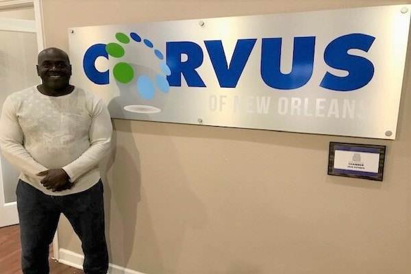 Corvus of New Orleans Franchisee Donald Valerie in front of Corvus sign