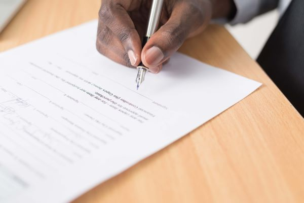 Man's hand signing a franchise disclosure document